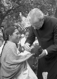 Don Álvaro bendice a unha muller e ao seu fillo.