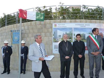 Il gonfalone della città di Ragusa sotto la targa, ancora coperta, con il nome del fondatore dell'Opus Dei.