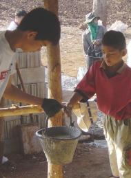 Sean passe un seau de ciment à l'un des enfants qui a collaboré avce le groupe