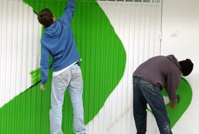 Grafiteros pintando la puerta metálica del garaje