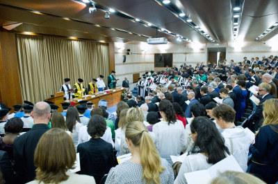 Los asistentes rezan una oración al inicio del acto académico.