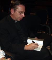 Firmando una copia de su libro
