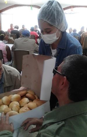 Peregrina de Arboleda en un hogar de adultos mayores, repartiendo pan que ellas hicieron para los abuelitos