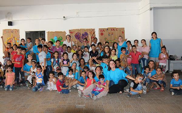 Les voluntàries amb el nens del camp del treball. Al fons de la imatge amb samarreta blanca  l'Andrea