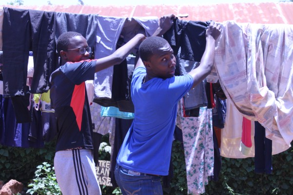 Mark and Brandon dry the clothes they had washed during the Form 3 Class visit to Alpha Joy Children's Home.