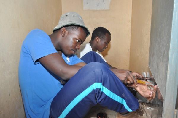 Jesse and Jeffrey work on repairing the doors of the dormitories of the children's home in Kisumu