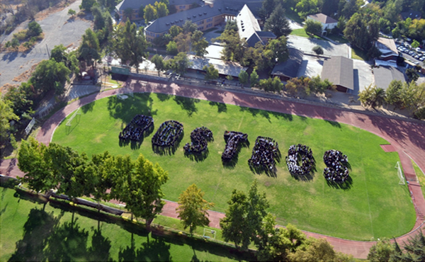 """Vista panorámica de 1400 alumnos, apoderados, profesores, administrativos del colegio Tabancura formando la palabra """"Rostros""""."""