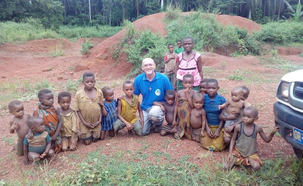 El padre Andrés, de los misioneros de la Consolata, enseña a los niños a leer y escribir.