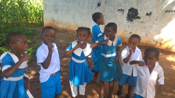 Kindergarten children learning how to brush their teeth, some for the first time