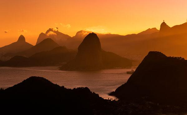 Quando o avião se aproxima do Rio de Janeiro, o sol põe-se sobre a baía de Guanabara, iluminando a cidade