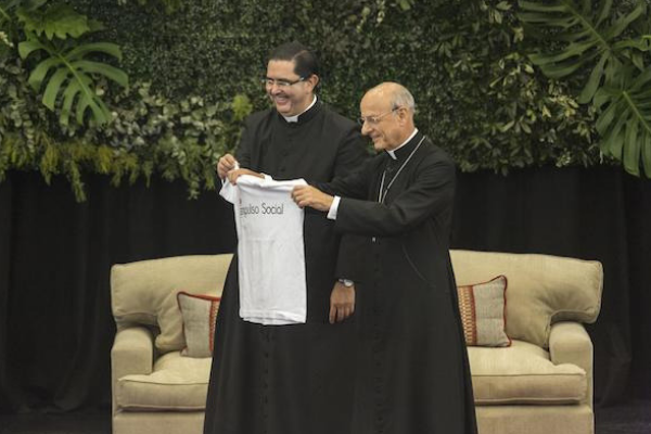 El Prelado del Opus Dei, Mons. Fernando Ocáriz, junto con el padre Víctor Urrestarazu (Vicario Regional del Opus Dei en Argentina, Paraguay y Bolivia) sosteniendo la remera de Impulso Social durante su visita al país.