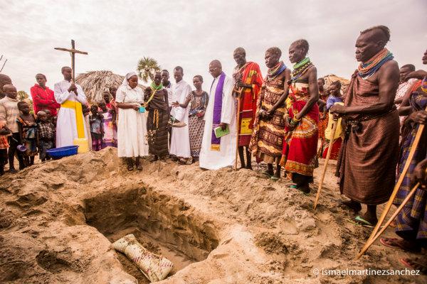 La madre, que ha perdido el segundo hijo en tres años, es la primera en lanzar arena al saco de su hijo en la tumba abierta en la arena junto a la choza familiar (Kenia). AYUDA A LA IGLESIA NECESITADA.
