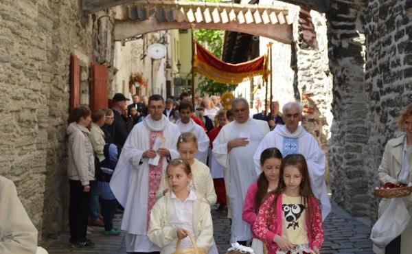 Uma procissão com o Santíssimo pelas ruas da cidade medieval de Viru Nigula (Estônia). Grupos de crianças jogaram pétalas de flores diante da passagem do Senhor.