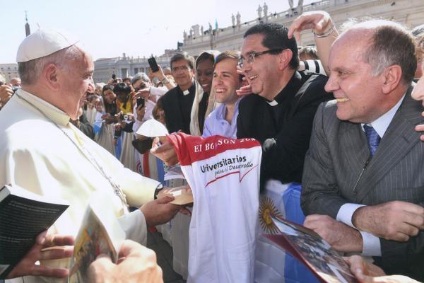 El padre Víctor Urrestarazu (Vicario Regional del Opus Dei en Argentina, Paraguay y Bolivia, y también capellán de la ong) entregando la remera de Universitarios para el Desarrollo al Papa Francisco