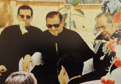 Un momento de la tertulia, en donde San Josemaría escucha con atención una canción interpretada por varias personas presentes.