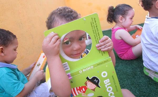 Alunos da Creche Rainha da Paz em atividade de leitura e exploração dos livros.