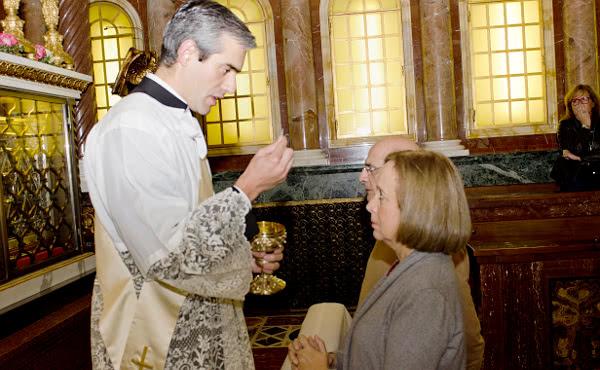 El diácono da la comunión a sus padres, Marta y Manuel.