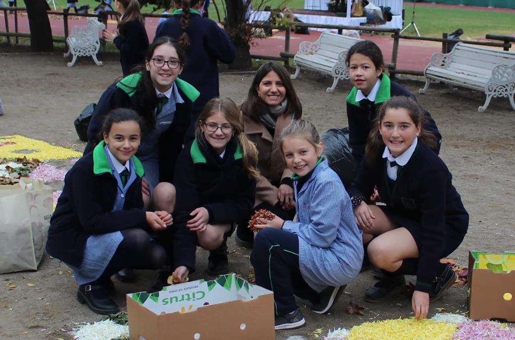 Alumnas del Colegio Huelén preparan la alfombra de flores, junto a una de las profesoras del colegio.