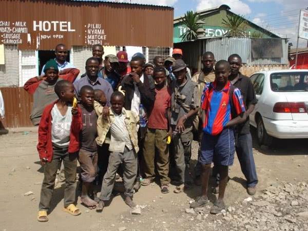 Moses Muthaka am Baugelände, umringt von Buben aus dem Slum
