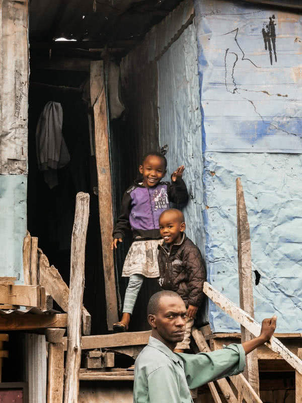 A father at the entrance of the slum, with a serious face, probably aware of his reality and the children next to him smiling because it is the only reality they know