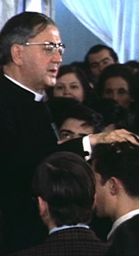 Während des Gebetes des Angelus am 7. Juli 1974 in Santiago de Chile. Der hl. Josefmaria legt mit einer liebevollen Geste seine Hände auf den Kopf eines der anwesenden Jugendlichen.