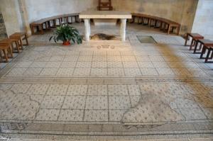 Attorno all'altare si trovano le tracce più importanti: la pietra venerata come il luogo in cui il Signore appoggiò i pani e i pesci, e il mosaico che conferma questa tradizione. Firma: Leobard Hinfelaar.