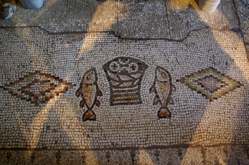 Il mosaico con il cesto di pani affiancato dai due pesci è datato fra la fine del V secolo e gli inizi del VI. Firma: Berthold Werner (Wikimedia Commons).