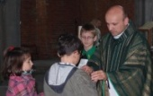 Ks. Marian Sikora błogosławi różańce dzieciom (autor obu zdjęć z ks. Marianem: Zofia Armata)